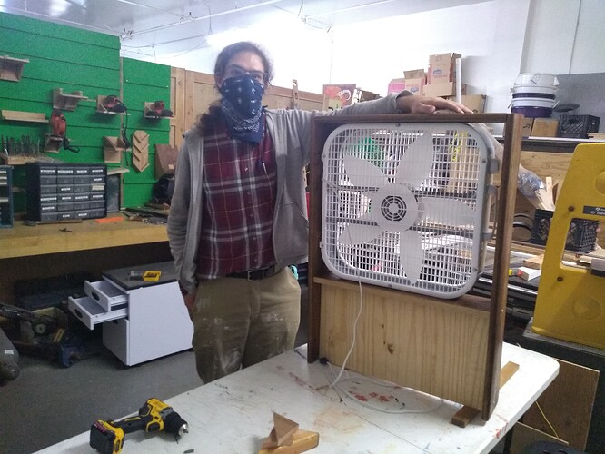 In the woodshop: Wolf stands next to a box fan in a wooden frame.